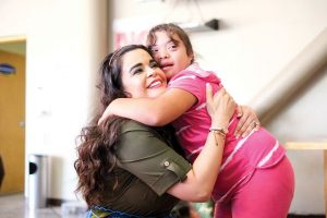 woman with down syndrome hugging someone