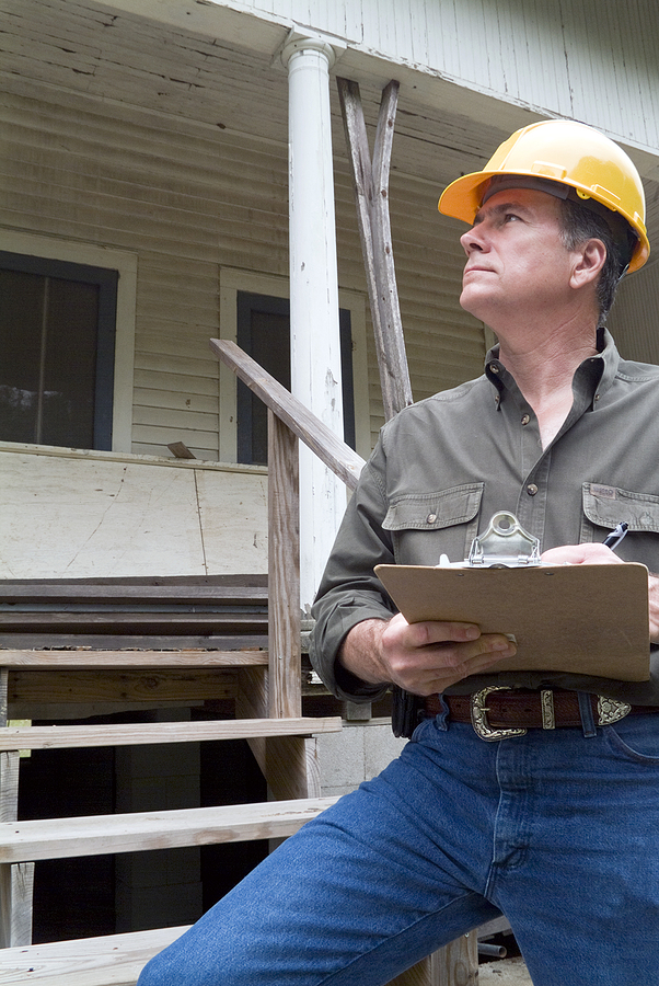 A man in a hard hat completing a building condition report