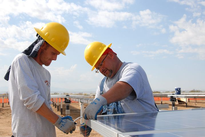 two men installing a 3 phase solar inverter