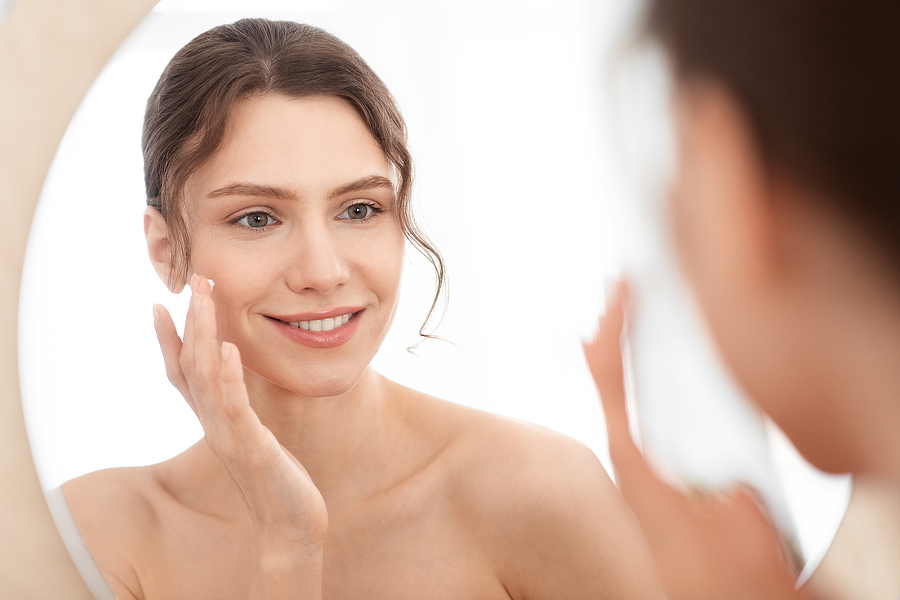 Beautiful woman using TheCOHub skincare products