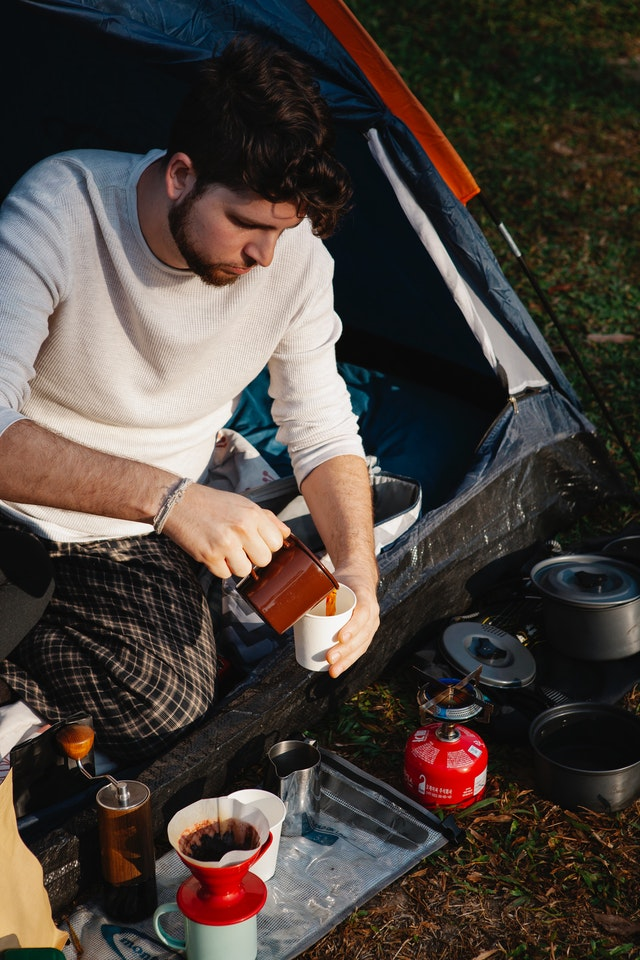 Man preparing coffee outside his camping tent