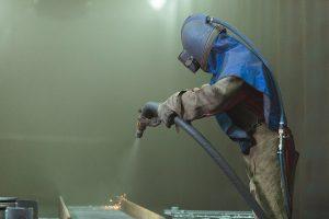 Worker doing an abrasive blast